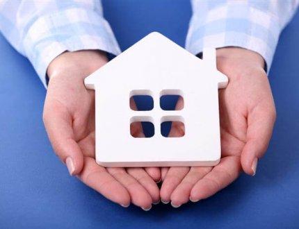יועץ משכנתא מחזיק דגם של בית בידיים