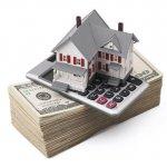 דגם של בית על מחשבון וערימה של שטרות כסף