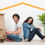 זוג יושב מתחת למסגרת של בית לאחר שקיבל משכנתא