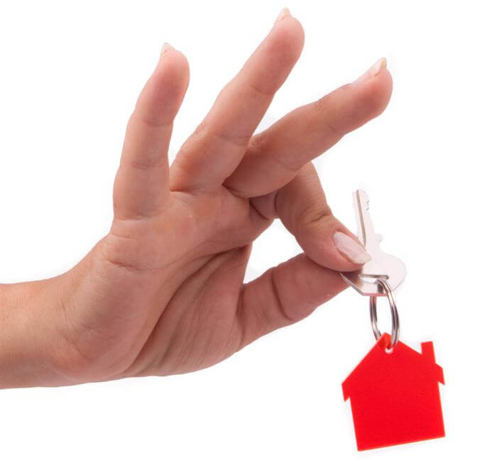 יד שאוחזת מחזיק מפתחות עם בית עליו