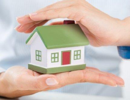 אדם שומר על דגם של בית בידיו
