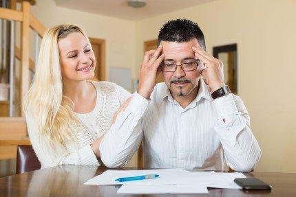 אדם מסתכל על טפסי משכנתא ואשה יושבת מאחריו