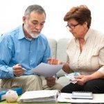זוג שנתקל בקשיים בתשלום משכנתא יושב על ספה ובודק אפשרויות תשלום