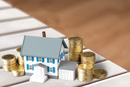 דגם של בית מונח לצד מטבעות