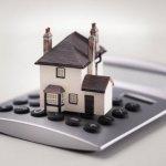 דגם של דירה במחיר למשתכן מונח על מחשבון